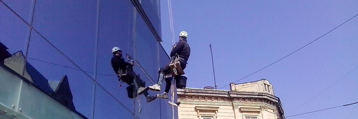 Миття вікон промисловими альпіністами на висоті